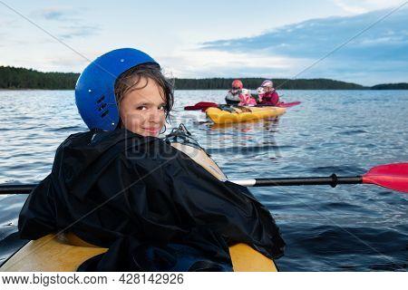 Teenage Caucasian Girl In Protective Helmet Tired But Happy In Kayaking Trip Sits In A Kayak On The