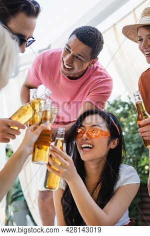 Joyful Multicultural Friends Clinking With Bottles Of Beer During Summer Party