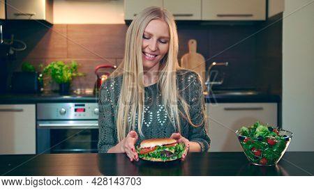 Young Lady Preferring Hamburger To Salad. Attractive Young Woman Choosing To Eat Healthy Hamburger F