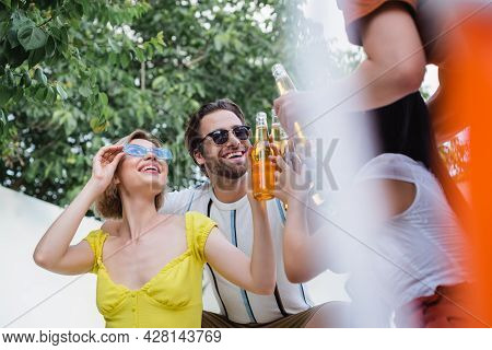 Happy Man Clinking Bottles Of Beer With Cheerful Women On Blurred Foreground