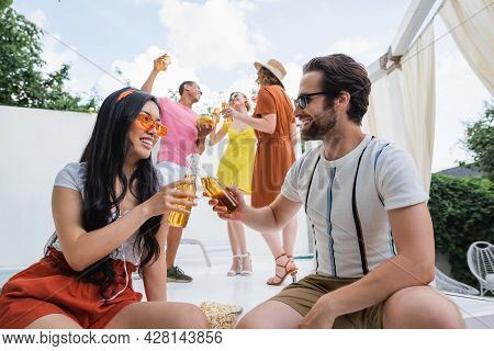 Happy Asian Woman Clinking Bottles Of Beer With Man Near Cheerful Multiethnic Friends On Background