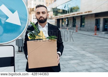 Depressed Jobless Person. Businessman Standing With Box Of Stuff Outdoors Near Road Sign, Free Space