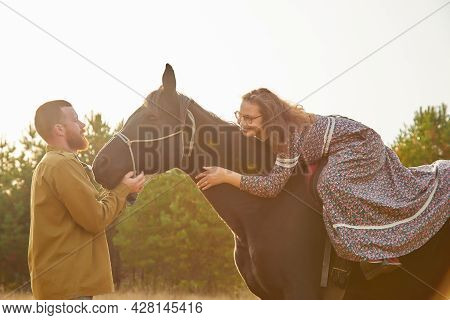 A Rural Couple With A Horse In A Natural Yellow Landscape On An Autumn Day. Young Man And Woman Toge