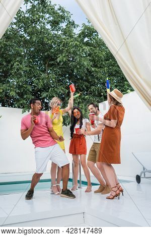 Cheerful Multiethnic Friends With Plastic Cups And Water Pistols Having Fun In Patio At Poolside