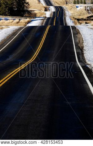 Hilly road for transportation and travel with double yellows lines roadway hills