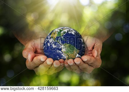 Double Exposure Of Hands Holding Planet Earth On Blurred Green Nature With Sunlight Background, Elem