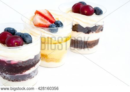 Thee Portions Of Sweet Cakes Decorated With Fresh Berries In A Row On White Background