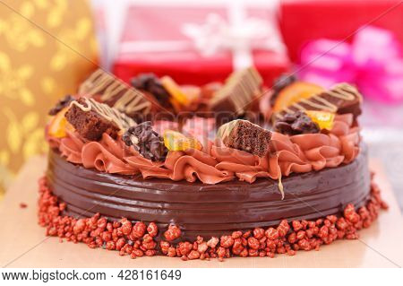 Chocolate Cake And Gift Boxes In Background