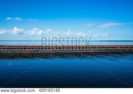 The Barge Floats On A Calm Water Surface. White Fluffy Clouds Blue Sky Above A Surface Of The Sea. B