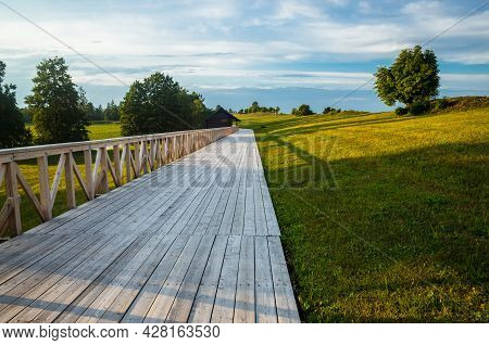 A Long Wooden Bridge, Pathway Or Road Made Out Of Planks And Logs With Wooden Handles Leading Throug
