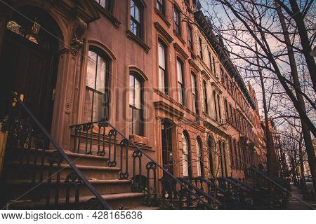 Row Of Old Brownstone Buildings Along An Empty Sidewalk Block In The Greenwich Village Neighborhood