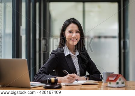 Portrait Of Business Woman And Lawyers Discussing Contract Papers With Brass Scale On Wooden Desk In