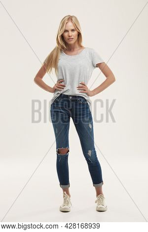Young confident european girl with hands on hips and looking at camera. Front view of blonde female teenager with blue eyes wear white t-shirt and jeans. Isolated on white background. Studio shoot
