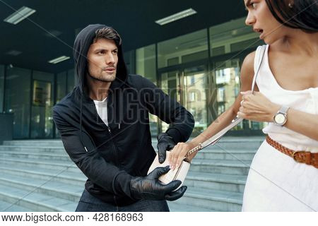 Aggressive robber want to steal handbag of frightened girl. Male bandit wear black hoodie and gloves. Young european brunette woman wear white dress. Concept of robbery. City daytime