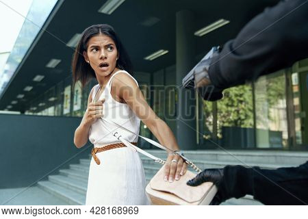 Robber want to steal handbag of scared girl. Cropped image of bandit wear black hoodie and threatening with pistol to young european brunette woman. Concept of robbery. City daytime