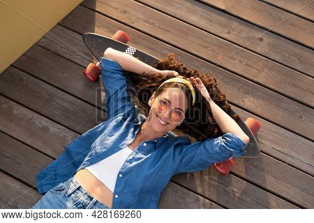 Carefree Young Hipster Woman On Skateboard Relaxed And Happy Smiling. Trendy Girl Skateboarder Lying