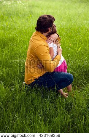Loving Father Cuddling Young Daughter As They Walk Through Field Together