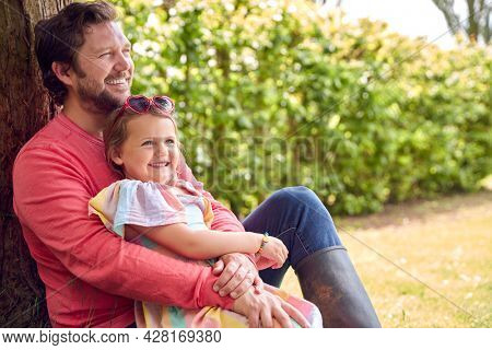 Loving Father Cuddling Young Daughter Sitting Under Tree In Garden Together