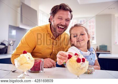 Father And Daughter In Kitchen Decorating Ice Cream Dessert With Cream And Raspberries