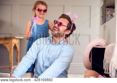 Father And Daughter Having Fun Playing With Dressing Up Box At Home