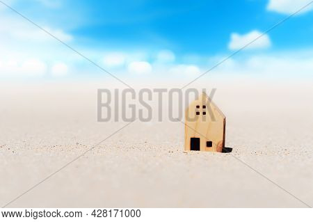 Small Home Model On Sand Beach With Blue Sky And White Clouds Background. Copy Space Of Family Lifes