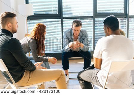 Portrait Of Depressed Young Man Telling About His Mental Problem Or Addiction To Other Patients Sitt