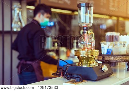Close Up To Barista Make Coffee With Vacuum Pot Syphon Brewer.  Syphon (siphon) Coffee Maker Brews D