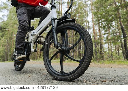 A Cyclist Rides On A Bike Path In The Forest. Riding An Electric Modern Bicycle. Cool Fashionable Bi