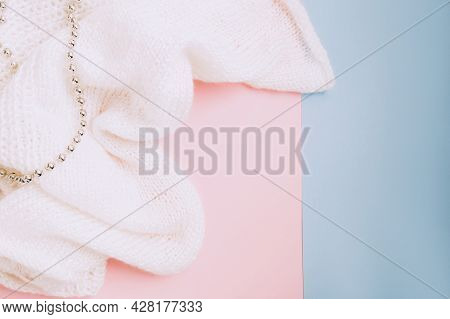 White Knitted Fabric And And Silver Beads On Pink And Blue Background. Craft On Black Background. Kn