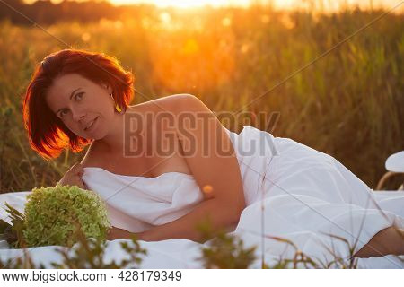 Charming Caucasian Woman 30-35 Years Old In White Bed In A Field With A Bouquet Of Hydrangea At Suns