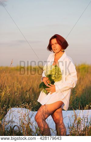 Charming Caucasian Woman 30-35 Years Old In A Field With A Bouquet Of Hydrangea In A White Men's Shi