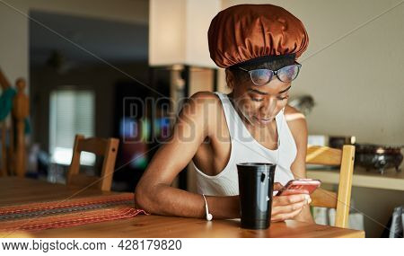 african american woman wearing showercap looking at smartphone during morning routine
