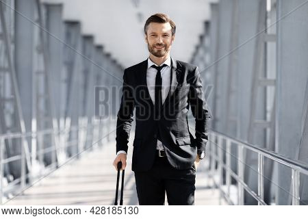 Wealthy Manager In Black Suit With Suitcase Posing In Airport