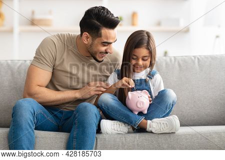 Little Girl And Dad Saving Money In Piggy Bank