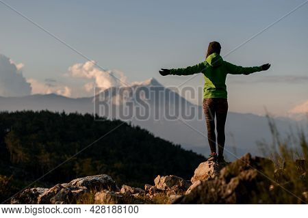 Rear View Of Woman With Outstretched Arms To Sides Against Beautiful Mountain Landscape