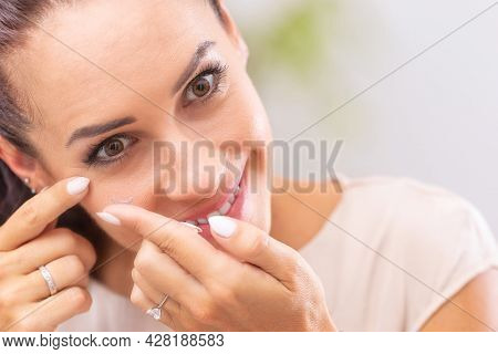 A Young Woman Puts Contact Lenses In Her Eyes.