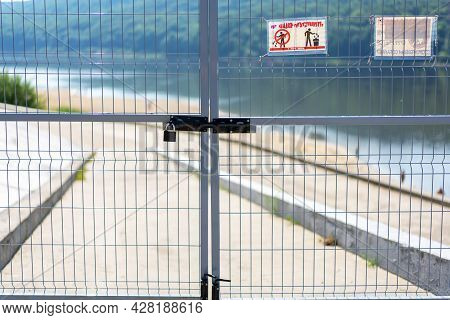 Metal Fence (gate) On The Background Of The River, Closed With A Lock. A Territory Free Of Covid-19.