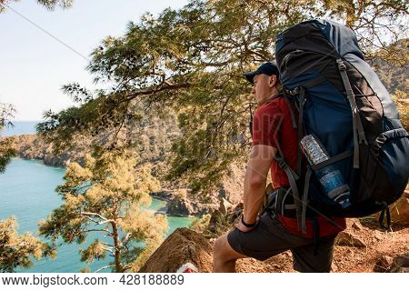 Man Hiker With Backpack Stand On Trail And Looks Towards The Sea Bay
