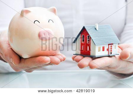 Manos sosteniendo una alcancía y un modelo de casa