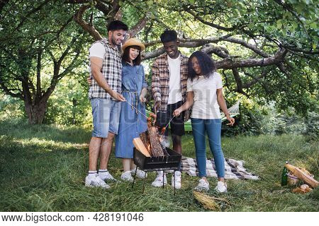 Group Of Four Multicultural Friends Gathering Around Barbeque For Grilling Sausages. Young People In
