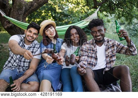 Four Joyful Friends Enjoying Grilled Sausages And Cold Beer During Picnic On Fresh Air. Multiracial