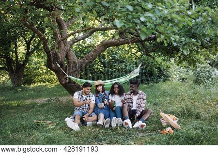 Young Carefree People Sitting On Grass, Eating Sausages And Drinking Beer. Four Multi Ethnic Friends