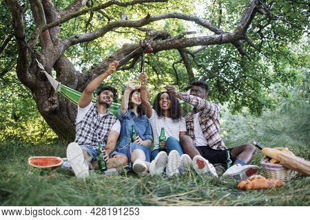 Four Young People In Casual Clothes Sitting Together At Green Garden And Enjoying Summer Picnic. Hap