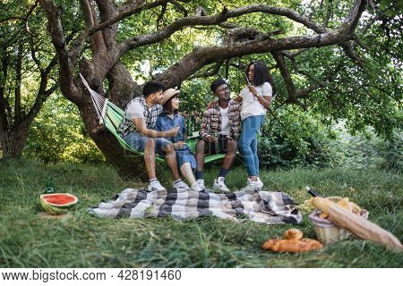 Group Of Four Multicultural Friends Eating Food And Drinking Beer During Leisure Time On Nature. You