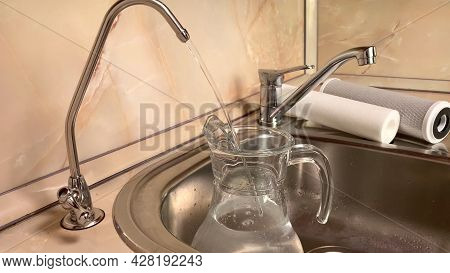 Pouring Filtered Water Into Glass Pitcher From Water Filter. Closeup Of Jug, Sink And Faucet. Drinka