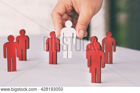 Many red wooden persons on the table and one person is painted in white color.