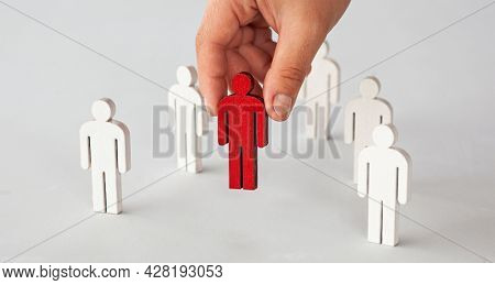 Many white wooden persons on the table and one person is painted in red color.