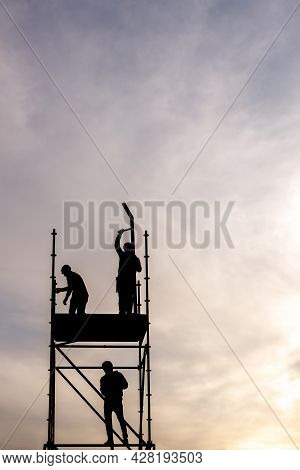 Moscow, Russia, May 02, 2021. Silhouettes Of Installation Workers Installing Metal Structures Agains