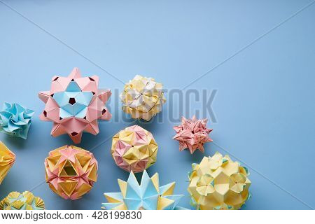 Set Of Multicolorhandmade Modularorigami Balls Or Kusudama Isolated On Blue Background. Visual Art