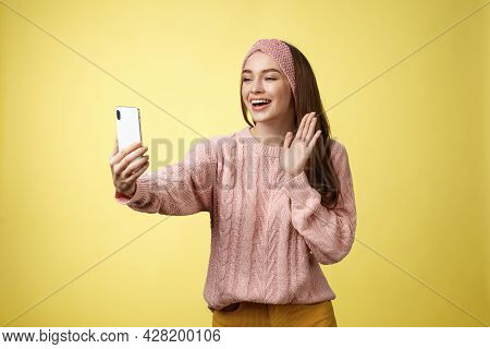 Charming Outgoing Girlfriend Having Online Video Chat, Holding Smartphone Waving At Phone Camera Say